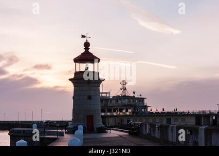 England, Ramsgate harbour. Lighthouse on end of jetty with harbour office behind. Dawn sky with sun hidden behind - Stock Photo