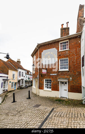 Cobbled Quay Hill and an alleyway of quaint local shops and historic buildings on Quay Street, Lymington, Hampshire - Stock Photo