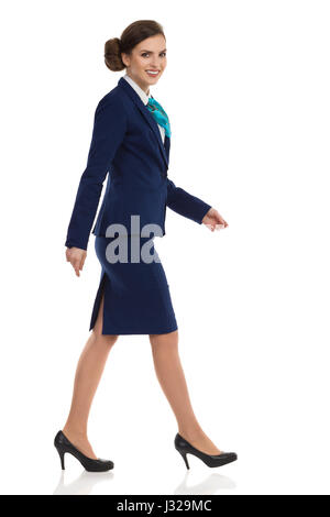 Beautiful young woman in blue suit, skirt and black high heels walking and looking at camera. Side view. Full length - Stock Photo