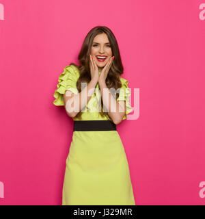 Smiling young woman in lime green dress posing with hands on chin and looking at camera. Three quarter length studio shot on pink background.