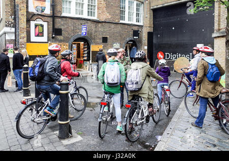 Tourists on a bike tour of London listed to their guide in London's Brick Lane, a popular tourist destination in - Stock Photo