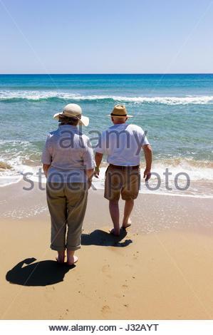 Senior man and woman tourists paddling in the Mediterranean Sea at Golden Sand Beach on the Karpasian Peninsula, - Stock Photo