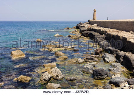 The rocky shore line, harbour wall and lighthouse, Kyrenia, northern Cyprus - Stock Photo