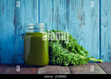 a kale smoothie served in a glass mason jar and a leaf of kale on a wooden surface against a blue rustic wooden - Stock Photo