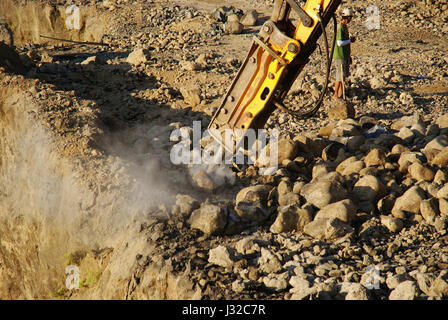 Mining construction industry, excavator digging granite or rock in quarry - Stock Photo