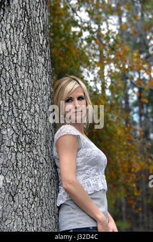 Arkansas leaves surround young woman as she leans against tree trunk.  She is wearing a grey T shirt with lacy over - Stock Photo