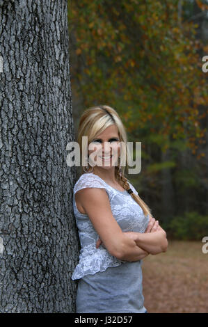Beautiful young woman smiles as she leans against a tree trunk in southern Arkansas.  Fall has colored leaves golden - Stock Photo