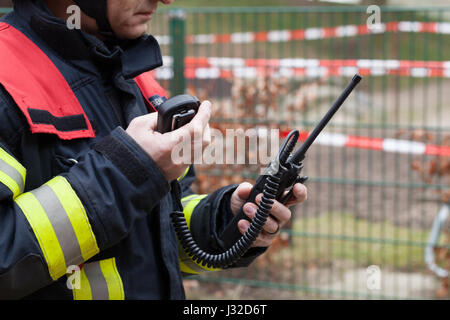 German firefighter leader used a walkie talkie in action - Stock Photo