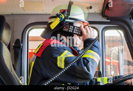 German firefighter drives in a fire truck in action and used a walkie talkie - Stock Photo