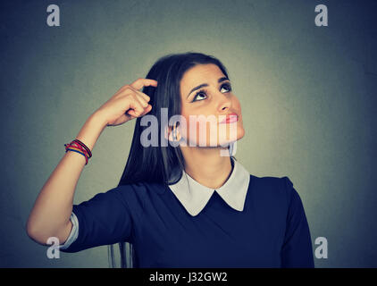 Portrait confused thinking young woman bewildered scratching her head seeks a solution looking up isolated on gray - Stock Photo