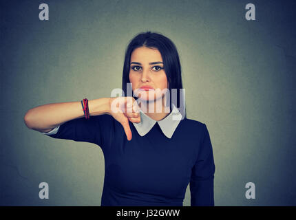 Unhappy woman giving thumb down gesture looking with negative expression and disapproval on gray background - Stock Photo