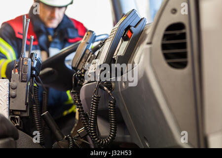 Firefighter drives a emergency vehicle with communication interior view and trowel - Stock Photo