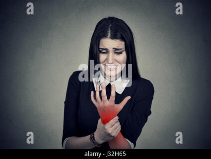 Young woman holding her painful wrist colored in red  isolated on gray wall background. Sprain pain - Stock Photo