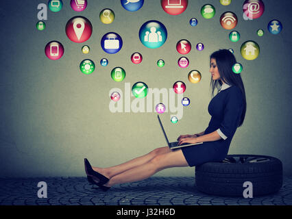 Young woman sitting on a tire working on laptop computer with social media application icons flying out of screen. - Stock Photo