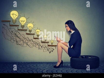 Happy young woman sitting on a wheel in front of growing up light bulbs. Business education success, promotion, - Stock Photo