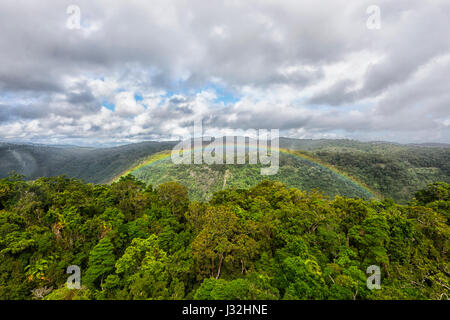 Rainbow over the canopy of pristine tropical rainforest viewed from Skyrail Rainforest Cableway, Cairns, Far North - Stock Photo