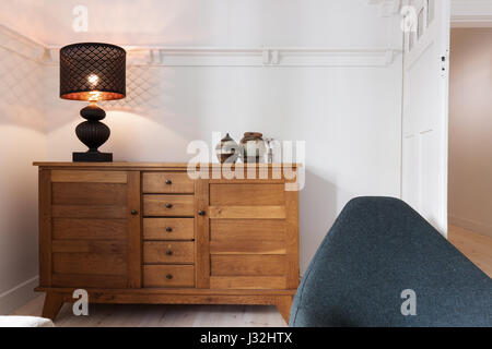 Illuminated lamp on sideboard buffet in luxury living room - Stock Photo