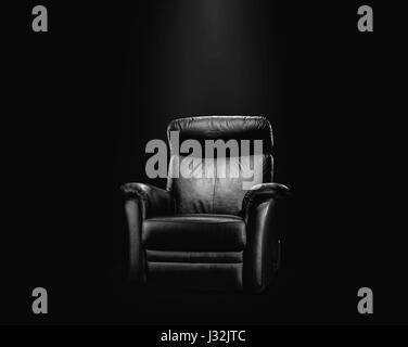 Black leather armchair in spotlight, dark background - Stock Photo