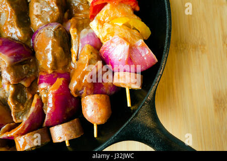 Delicious kebabs with marinated pieces of meat, fresh vegetables and sliced sausages strung on wooden skewers - - Stock Photo