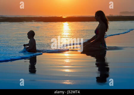 Family swimming fun on black sand beach with sea surf. Happy mother, baby son sit and look at ocean on sunset sky - Stock Photo