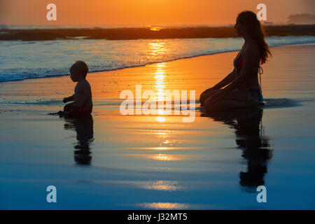 Family swimming fun on black sand beach with sea surf. Happy mother, baby son sit and look at ocean on sunset sky with sun background. Child with pare