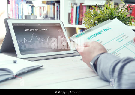 Tablet pc with internet usage application and man holds bill for internet. Internet usage application made in graphic - Stock Photo