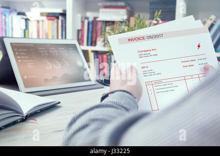 Man holds invoice of electric power usage - Stock Photo