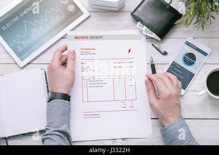 Man holds invoice of electric power usage over desk with tablet and smartphone with applications made in graphic - Stock Photo