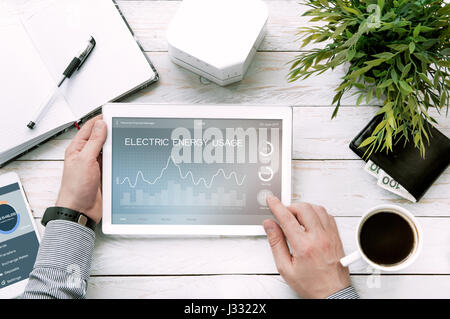 Man holds tablet pc with electric energy usage application made in graphic program - Stock Photo