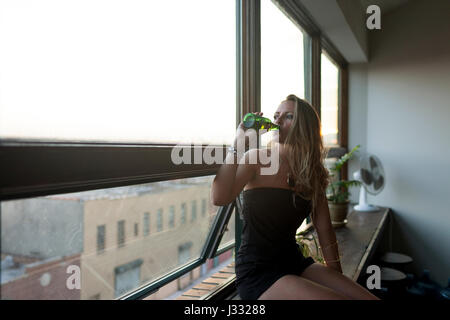 Young woman drinking a beer while looking out a window - Stock Photo