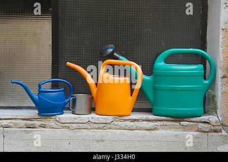Three watering cans - Stock Photo