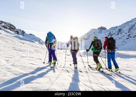 Group of people on a ski tour over the Oberaarjoch lake at morning light, Grimselpass, Wallis, Switzerland - Stock Photo