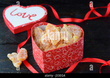 Heart shaped box full of candied orange slices. Lid in a shape of heart with love word, red ribbon on a black background. - Stock Photo