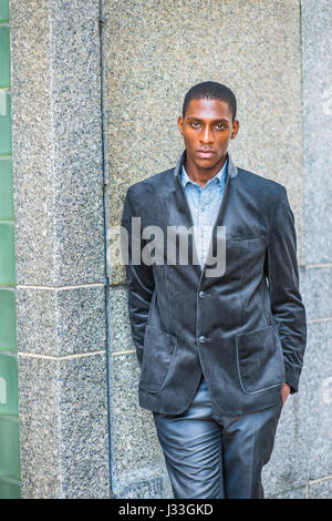 Young African American Man wearing new style black blazer, two hands putting in pockets, standing against wall on - Stock Photo