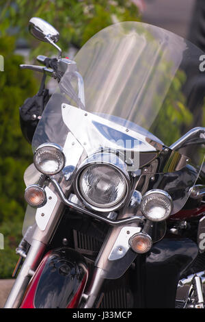 Classic motorcycle with a protective windscreen and safety helmet on the steering wheel on the background of greenery. - Stock Photo