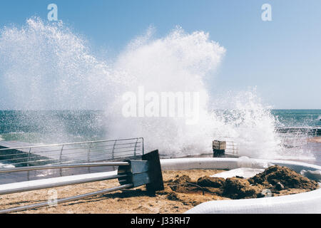 Big waves breaking on the embankment and cause damage. Sunny and windy weather. - Stock Photo