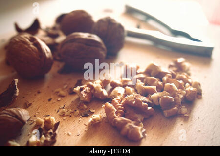 Walnuts and nutcracker on a wooden board. - Stock Photo