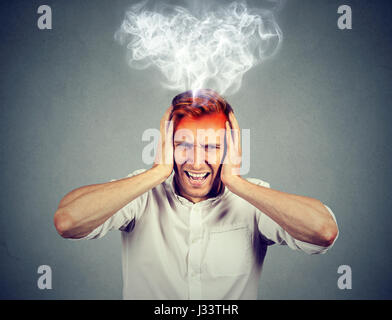 Portrait young stressed man screaming frustrated overwhelmed steam coming out up of head isolated on grey wall background. - Stock Photo