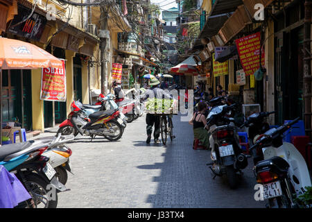 HANOI, VIETNAM - MAY 10: Vietnamese flower vendor walking down the street of Hanoi with his bicycle on May 10, 2014 - Stock Photo