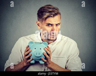 Young greedy stingy business man holding piggy bank isolated on gray wall background - Stock Photo
