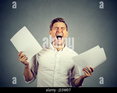 Angry stressed screaming business man with documents papers paperwork isolated on gray wall background. Negative - Stock Photo