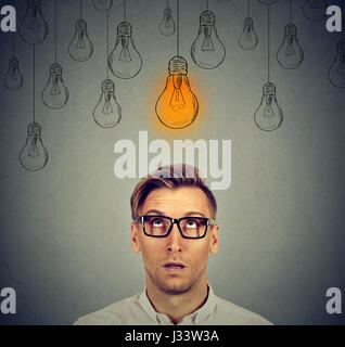 Thoughtful man in glasses looking up with light idea bulb sign above head has an idea isolated on gray wall background - Stock Photo