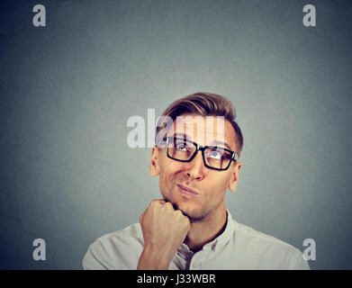 confused skeptical man thinking looking up isolated on gray background with copy space above head. Human face expressions, - Stock Photo