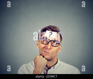 thinking man with question mark on gray wall background - Stock Photo