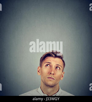 Headshot confused man thinking looking up isolated on gray wall background with copy space above head. Human face - Stock Photo