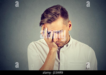 Closeup portrait sad young handsome man with worried stressed face expression looking down - Stock Photo