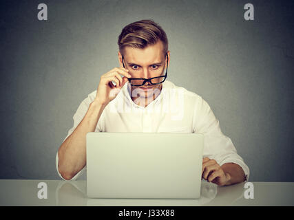Confused shocked man looking at his laptop - Stock Photo
