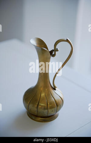 Old bronze pitcher on a light background. Retro Oriental style - Stock Photo