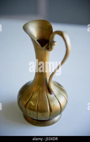 Old bronze pitcher on a light background. Retro Oriental style - Stock Photo