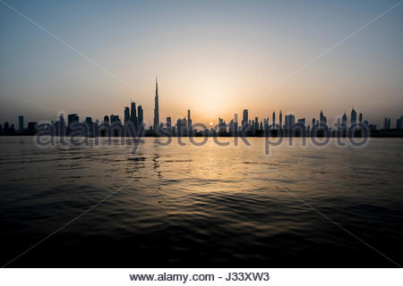Silhouette of Dubai during a nice sunset on the city, view from the water canal, Ras Al Khor side. United Arab Emirates - Stock Photo